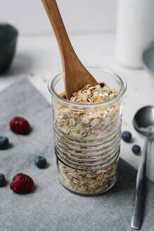 Wooden spoon in jar of granola - JMHMF00034