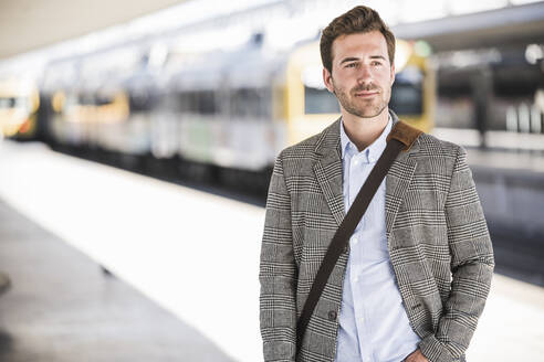 Portait of confident young businessman at the train station - UUF20142
