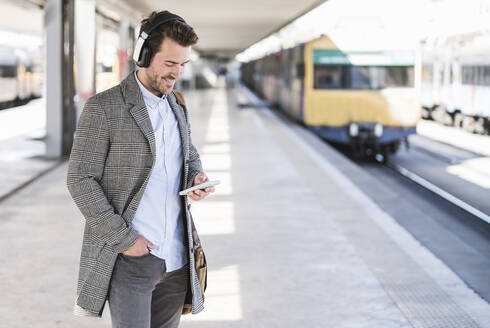 Young businessman with cell phone and headphones at the train station - UUF20148