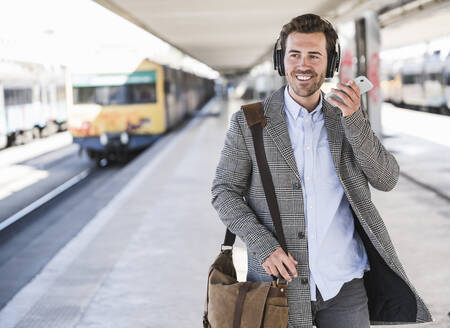 Smiling young businessman with cell phone and headphones at the train station - UUF20151