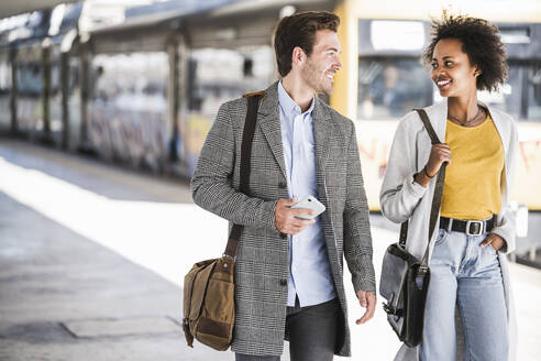 Happy young businessman and businesswoman walking and talking at the train station - UUF20154