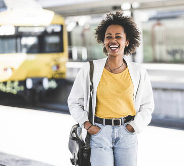 Laughing young woman at the train station - UUF20157