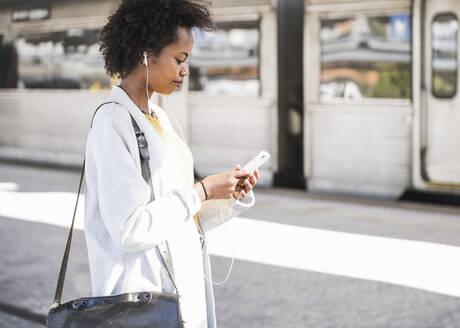 Young woman with cell phone and earphones at the train station - UUF20160