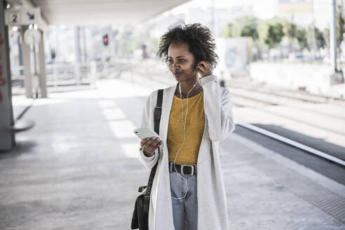 Young woman with cell phone and earphones at the train station - UUF20163