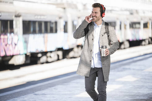 Happy young businessman with coffee mug and headphones walking at the train station - UUF20169