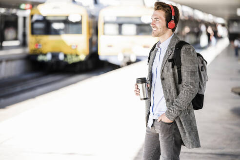 Smiling young businessman with coffee mug and headphones at the train station - UUF20172