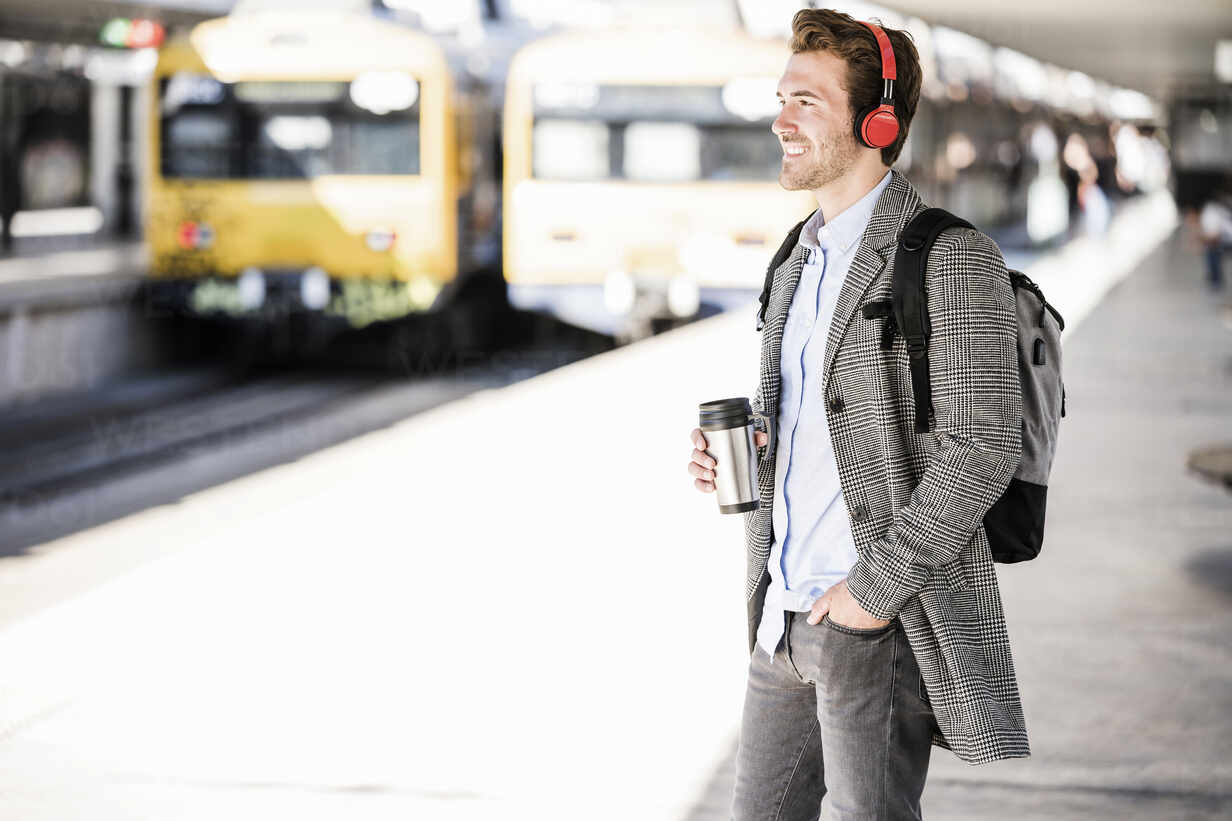 Smiling young businessman with coffee mug and headphones at the train station - UUF20172 - Uwe Umstätter/Westend61
