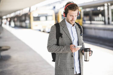 Young businessman with cell phone and headphones at the train station - UUF20175