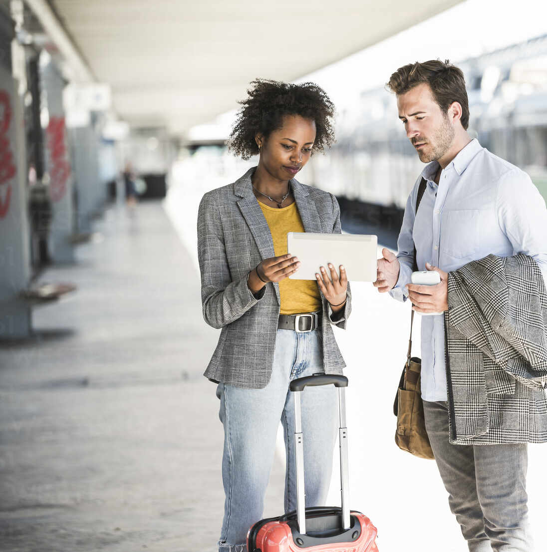 Young businessman and businesswoman using tablet together at the train station - UUF20184 - Uwe Umstätter/Westend61