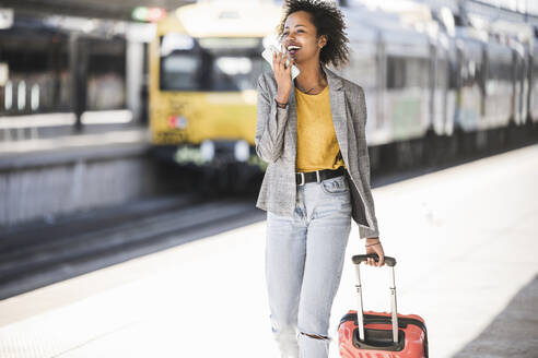 Happy young woman using cell phone at the train station - UUF20193