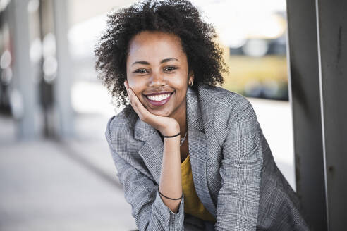 Portrait of smiling young businesswoman at the train station - UUF20205