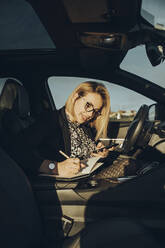Young blond woman using smartphone in the car, writing in a notebook - MTBF00310