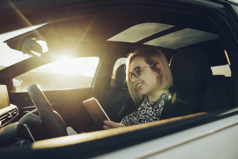 Young blond woman using smartphone in the car - MTBF00313