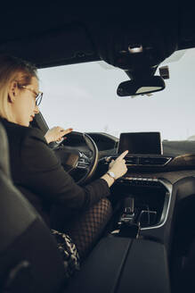 Young woman using navigation device in car - MTBF00316