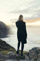 Rear view of young blond woman with smartphone at the coast during sunset - MTBF00319