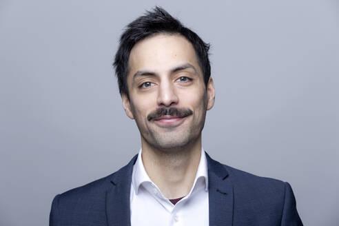 Portrait of smiling businessman with moustache - FLLF00377