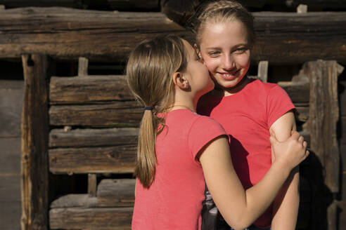 Girl embracing and kissing her sister - PSIF00357