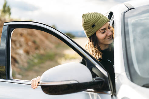 Smiling Woman Sitting In Car During Road trip - TGBF02139