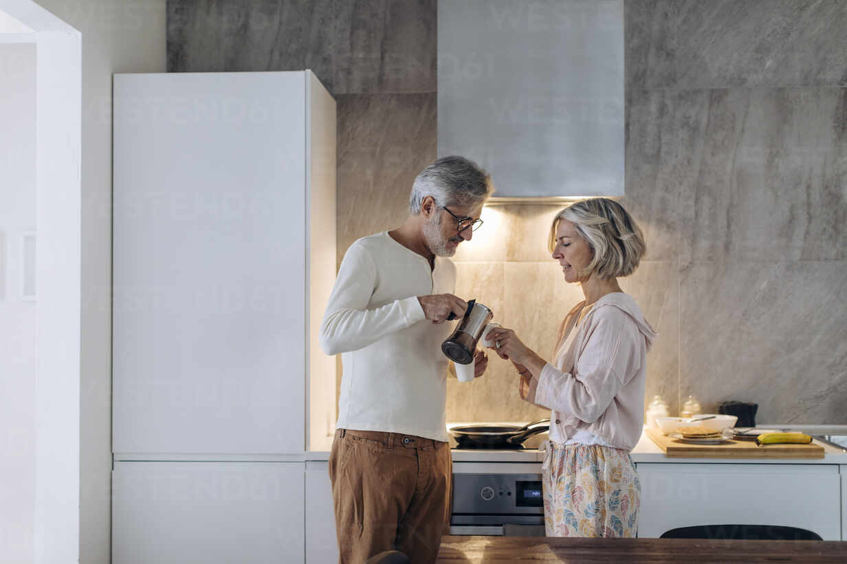 Mature couple in kitchen at home in the morning – Stockphoto