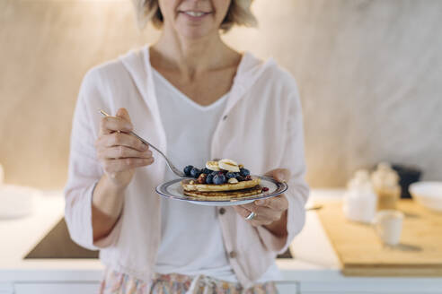Close-up of woman holding a plate with pancakes and fruit - SODF00530