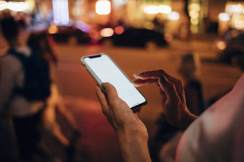 Hands of woman holding smartphone at night, close-up - OYF00088