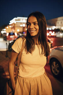 Young smiling woman in the city at night - OYF00091
