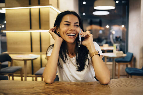Black-haired woman using smartphone in cafe - OYF00100