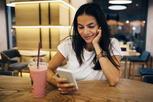 Black-haired woman drinking a smoothie and using smartphone in cafe - OYF00103
