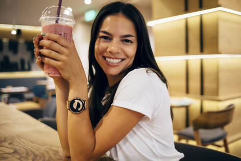 Black-haired woman drinking a smoothie in cafe - OYF00109