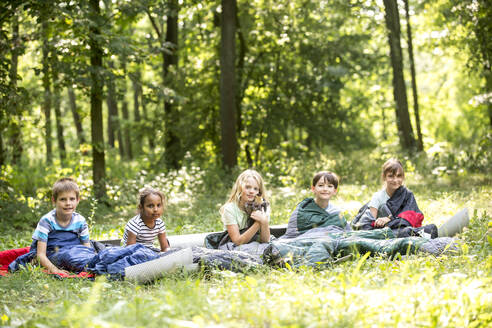 children camping in forest, sitting in their sleeping bags - WESTF24553