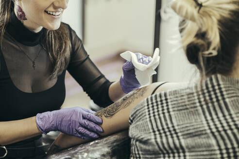 female tattooist tattooing upper arm of female customer - MTBF00339