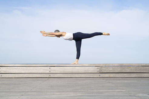 Woman practicing yoga on pier - JOHF05506