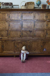Unhappy little girl sitting on the floor in front of big cabinet - PSIF00366
