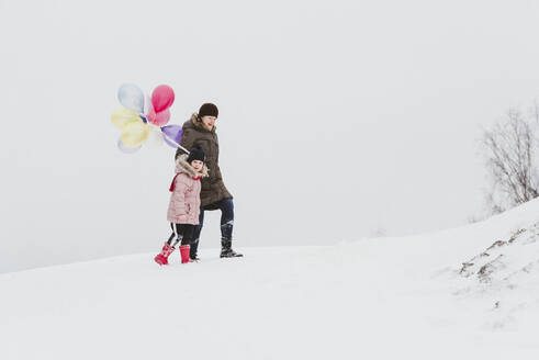 Mother and little girl with balloons walking in snow-covered landscape - PSIF00372