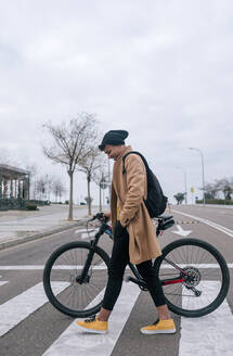 Young man with bicycle crossing a street in the city - GRCF00085