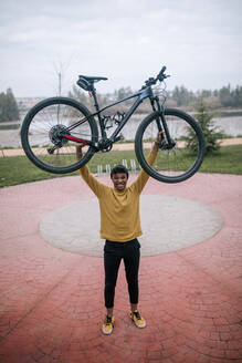Portrait of happy young man lifting a bicycle - GRCF00094