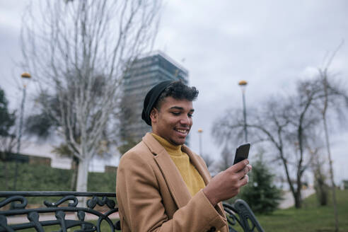 Smiling young man sitting on a bench using cell phone - GRCF00100