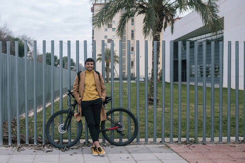 Portrait of smiling young man with bicycle in the city - GRCF00103