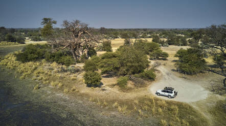 Aerial view of an isolated white jeep in a dirty track and a big Baobab tree, Bwabwata National park, Namibia - VEGF01416