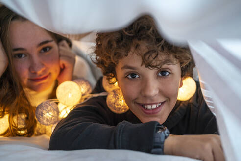 Portrait of happy brother and sister with chain of lights underneath bedcover - DLTSF00411