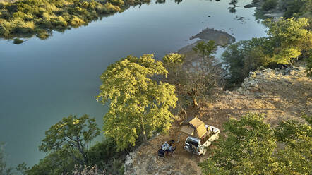 Aerial view of a couple camped with their jeep and rooftop tent and having breakfast in front of the river, Cunene river area, Angola - VEGF01439