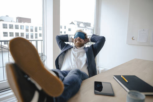 Businessman having a power nap at desk in office - GUSF03183
