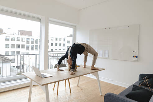Young businesswoman practicing yoga on desk in office - GUSF03192
