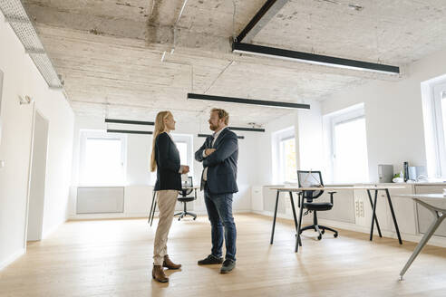 Businessman and businesswoman talking in office - GUSF03210