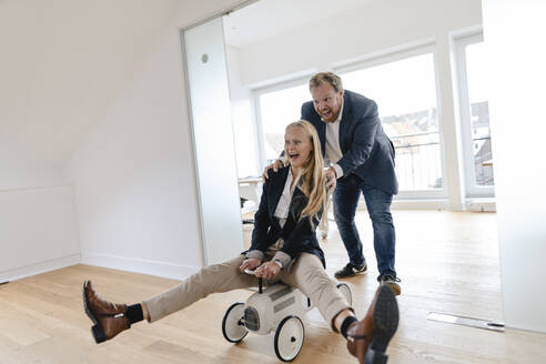 Playful businessman pushing businesswoman on toy car in office - GUSF03213