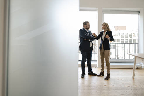 Businessman and businesswoman talking in office - GUSF03216