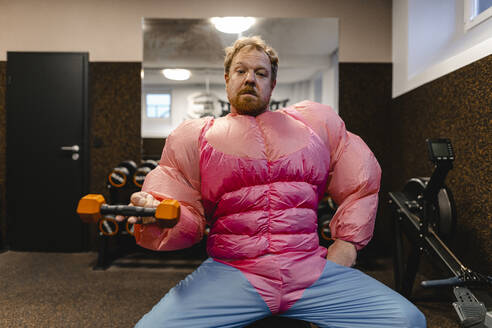 Man in gym wearing pink bodybuilder costume lifting dumbbell - GUSF03222