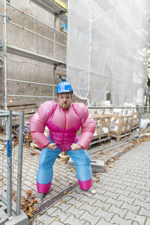 Portrait of man wearing pink bodybuilder costume and hard hat at construction site - GUSF03225