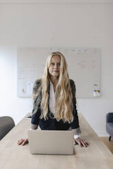 Portrait of young businesswoman practicing yoga on desk in office - GUSF03258