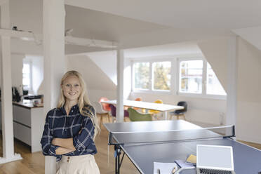 Portrait of young businesswoman in office with table tennis table - GUSF03267